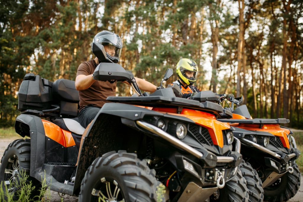 Two quad bike riders in helmets closeup, side view